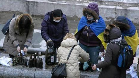 Mielenosoittajat valmistelevat polttopulloja keskiviikkoaamuna.