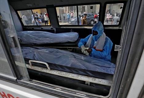 Suojapukuun pukeutunut mies istuu ambulanssissa, jossa on kahden koronaviruspotilaan ruumiit.