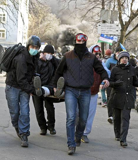 Loukkaantunutta mielenosoittajaa kannetaan Kiovan keskustassa.