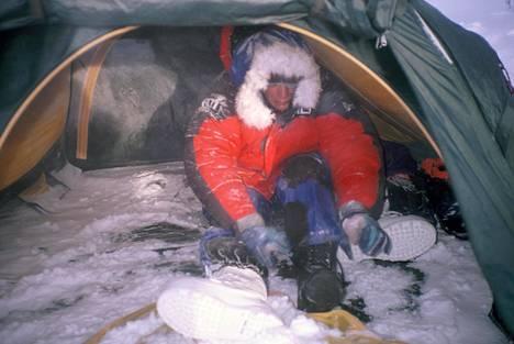 Tommi vetää hiihtomonoa jalkaansa onnettomuuspäivän aamuna 9.4. Teltta on viimeistä kertaa pystyssä, mutta lumimyrsky on paiskannut sen pohjan täyteen lunta. Tämä on viimeinen kuva, jonka ryhmän valokuvausvastaava Timo Polari otti Grönlannin kamaralta.