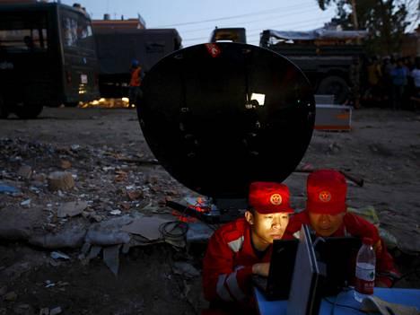 Kiinalaiset avustustyöntekijät viestivät kannettavan ja lautasantennin avulla.