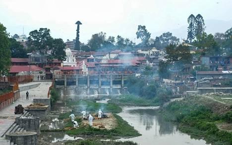 Koronaviruksen uhreja tuhkataan Bagmati-joen varrella.