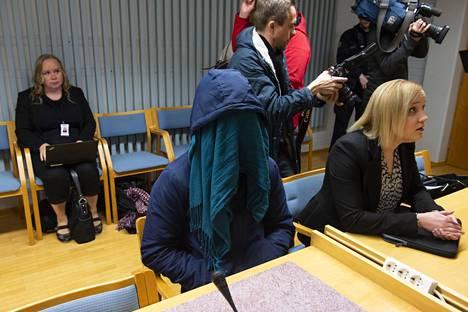 21-vuotias syytetty peitti kasvonsa kaulaliinalla.