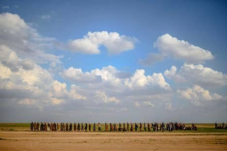 Baghuzista lähteneitä miehiä kävelemässä kohti SDF-joukkojen hallussa olevaa aluetta.