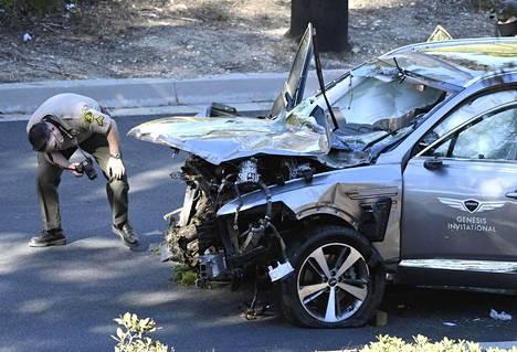 Poliisit tutkivat Woodsin auton vaurioita.
