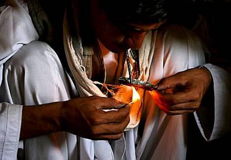 Afganistanilainen huumeriippuvainen mies polttaa heroiinia.