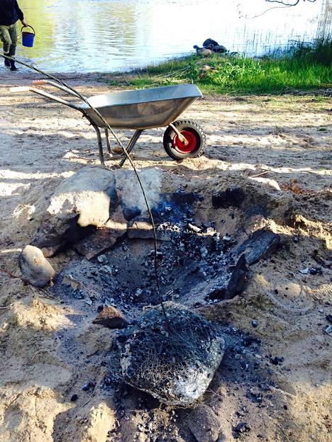 Nosta kuuma paisti kuopasta rautalankakahvaa apuna käyttäen.