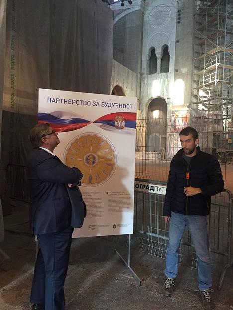 Timo Soini kuunteli Belgradissa Pyhän Savan ortodoksikatedraalin tarinaa. Taustalla kyltti kertoo Venäjän rahoittavan sen entisöintiä.