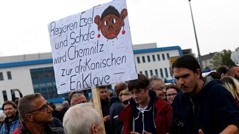 Äärioikeistolainen mielenosoittaja piteli esillä vihamielistä protestikylttiä torstaina Chemnitzissä.