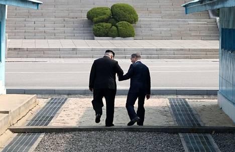 Historiallinen hetki: Pohjois-Korean ja Etelä-Korean johtajat ylittävät maiden välisen rajalinjan toisistaan kiinni pitäen.