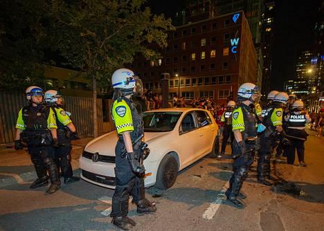 Poliisit suojasivat väkijoukon hajottamaa autoa Montrealin keskustassa.