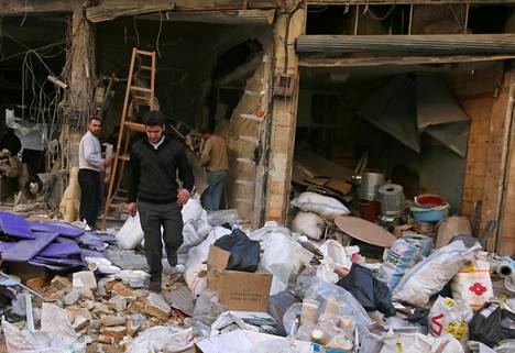 Miehet keräsivät tuhoutuneiden kauppojen tarvikkeita talteen al-Shaarin asuinalueella torstaina.