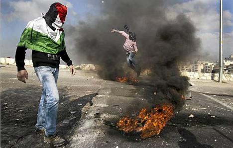 Palestiinalaismielenosoittaja heitti kiven Israelin turvallisuusjoukkoja kohti mielenilmauksen yhteydessä, joka järjestettiin vuoden 1976 mielenosoituksissa kuolleiden kuuden henkilön muistolle.