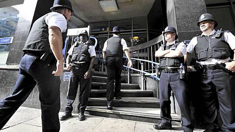 Poliiseja oikeustalon edessä Lontoossa.