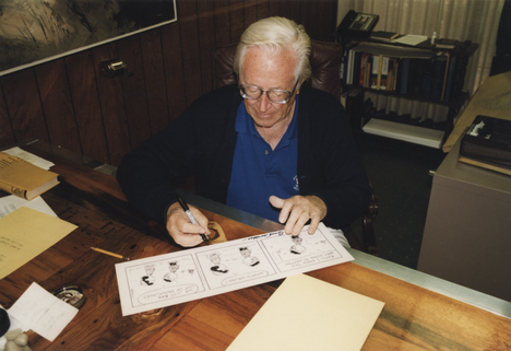 Charles M. Schulz signeeraamaassa alkuperäispiirrostaan, jonka hän lahjoitti Jyrki Vainiolle 1999.