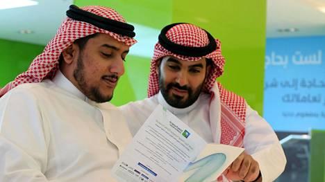 Miehet tutkivat Aramcon listautumisesitettä Riadissa, Saudi-Arabiassa sunnuntaina.