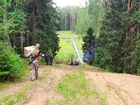 Latvialaiset jakamassa ruokaa Valko-Venäjän vastaiselle rajalleen saapuneille ihmisille.