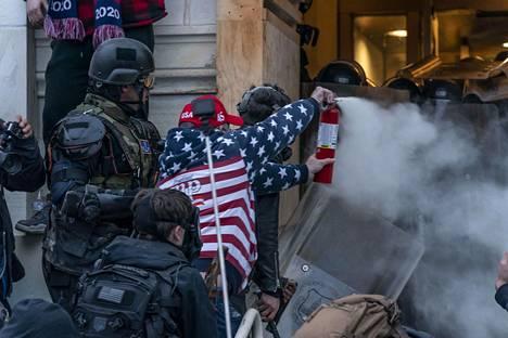 Presidentti Donald Trumpin kannattaja suihkuttaa poliisin päälle ilokaasuksi väitettyä kaasua yrittäessään tunkeutua Capitol-rakennukseen 6. tammikuuta.
