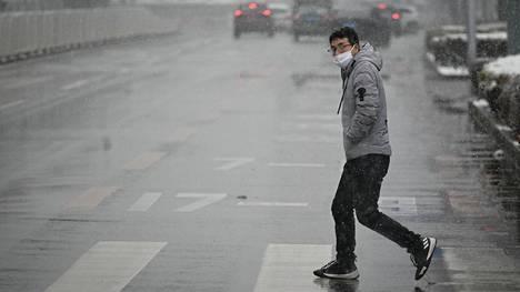 Mies piti maskia lumisena päivänä Pekingissä perjantaina.