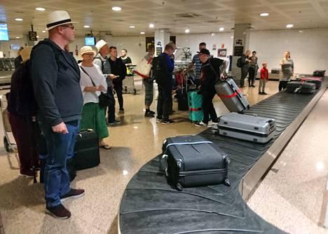 Matkustajat odottivat laukkujaan Barcelonan kentällä neuvottomana.
