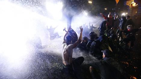 Poliisi käyttää vesitykkejä mielenosoittajia vastaan.