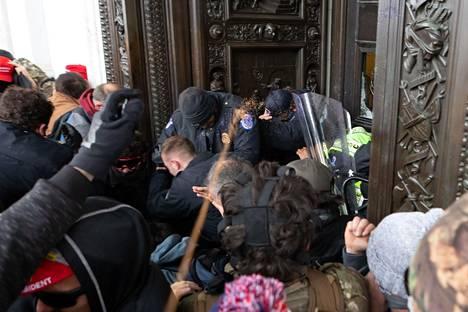 Poliisi ja väkijoukko otti yhteen yhdellä rakennuksen ovella.