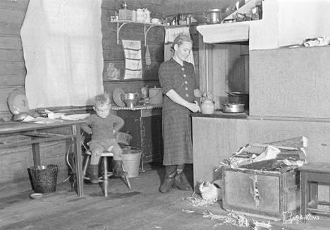 Heikki-poika istuu tyytyväisenä tuolilla äidin vieressä, ja venäläissyntyinen kissa kyyröttelee uunin luona. Sakkola 1941.11.04