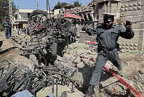 Afgaanipoliisi hyppi raunioissa autopommi-iskun jälkeen Kabulissa.