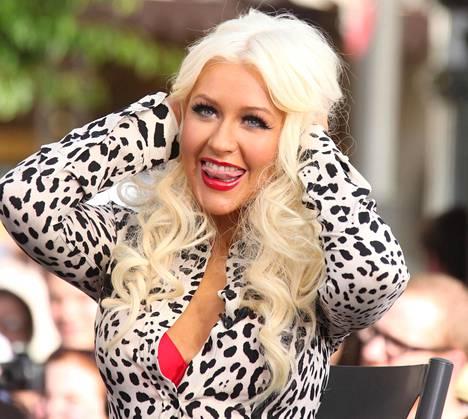Aguileran tavaramerkkejä ovat vaalea pöyheä tukka, punaiset huulet, näyttävät rajaukset ja yleensä poven paljastavat asut.