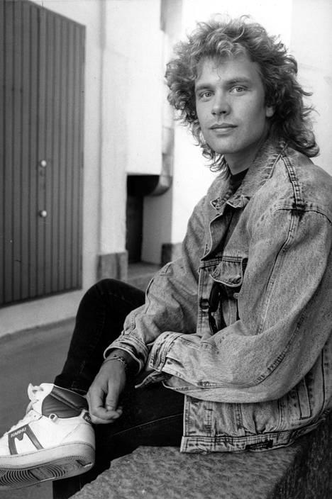Vuonna 1987 Tauskilla oli pitkä tukka, ja se oli kihartuvaa sorttia. Tässä lookissa laulaja muistuttaa kiistatta esimerkiksi laulaja Ilpo Kaikkosta.