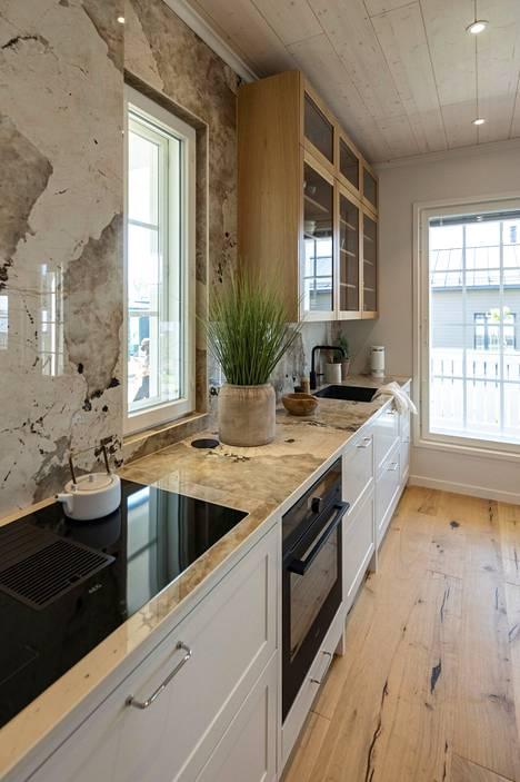 Keittiön kalusteet sekä lattia ja katto ovat kaikki saaneet pintansa kauniista luonnonmateriaaleista Designtalo Idyllissa.
