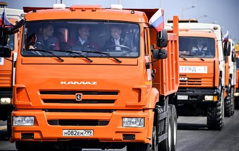 Ensimmäisenä sillalle ajoi pitkä raskaiden ajoneuvojen saattue, jota johti Putinin ajama kuorma-auto.