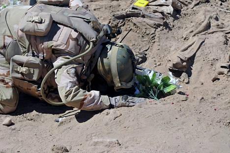 Sotilas rukoilee Isisin verilöylyssä kuolleiden shiiasotilaiden joukkohaudalla viime huhtikuussa.