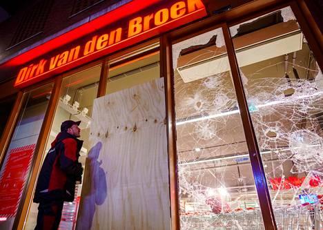 Työntekijä suojaa rikottua supermarketin ikkunaa.