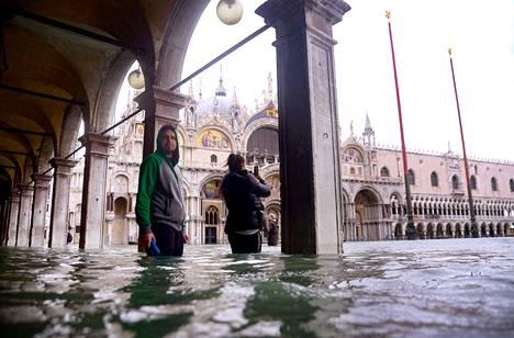 Turistit ottivat valokuvia tulvivasta Pyhän Markuksen aukiosta.