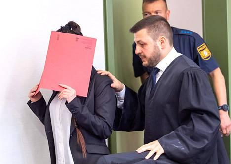 Syytetty peitti oikeudessa kasvonsa punaisella kansiolla.