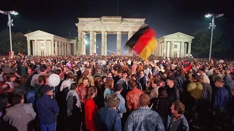 Berliiniläiset juhlivat Saksan yhdistymistä Brandenburgin portilla 3. lokakuuta 1990