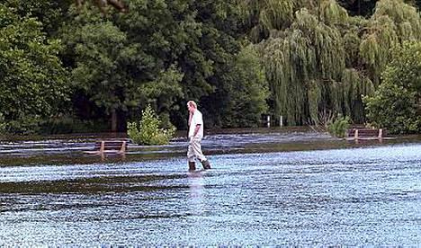 Mies kävelee tulvan valtaamalla pellolla Pangbournessa Englannissa.