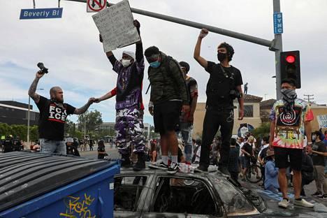 Ihmiset seisoivat poltetun poliisiauton päällä Los Angelesissa lauantaina.