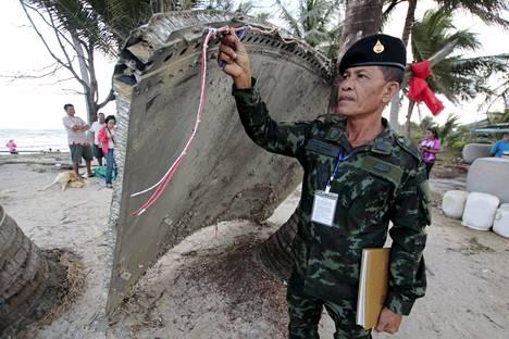 Thaimaalainen sotilas tutki sunnuntaina Nakhon Si Thammaratin provinssin rannikolta edellisenä päivänä löytynyttä metallikappaletta. Sen alkuperä on kuitenkin viranomaisten mukaan muualla kuin Malaysian Airlinesin kadonneessa matkustajakoneessa.