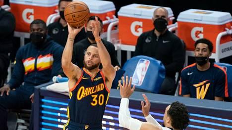 Golden State Warriorsin Stephen Curry heittää ennen kuin Memphis Grizzliesin Dillon Brooks ehtii estämään.