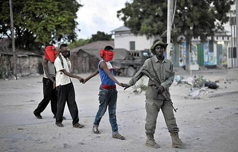 Mogadishun Wardhiigleyn alueella oli varhain tiistaina erikoisoperaatio, jossa pyrittiin kampaamaan esiin islamistiliike Al-Shahaabin edustajia. Turvallisen pääkaupungin asialla olivat nyt Somalian poliisi sekä Afrikan Unionin paikalliseen rauhaan tähtäävä ryhmä AMISOM. Kuvassa olevia kolmea miestä talutetaan viranomaisten väliaikaisselliin epäiltyjen Al-Shahaab yhteyksien vuoksi.