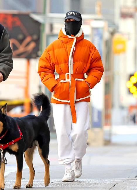 Sähäkkä oranssi ja puhdas punainen ovat talven kuumimmat toppavärit. Malli Emily Ratajkowski piilotteli talven suosikkiasusteen maskin takana.