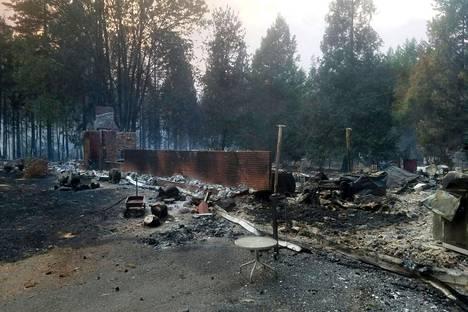 Palossa tuhoutunut talo McKenzie Bridgella Oregonissa keskiviikkona. Sadat elleivät tuhannet ovat menettäneet kotinsa metsäpaloissa.
