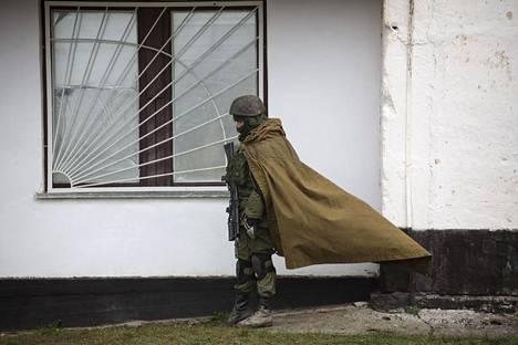 Venäläiseksi uskottu sotilas seisoi vartiossa Simferopolin lähellä sijaitsevassa Perevalnojen tukikohdassa Krimin kaappauksen aikoihin maaliskuussa 2014.