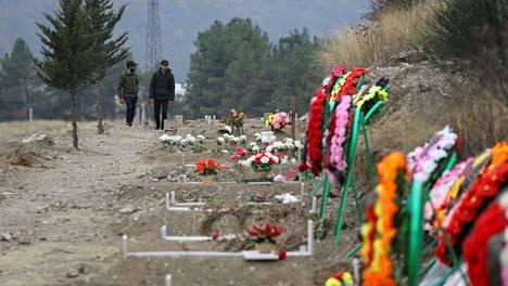 Miehet kävelivät taisteluissa menehtyneiden sotilaiden ja siiviilien hautojen ohi Stepanakertissa, Vuorist-Karabahissa.