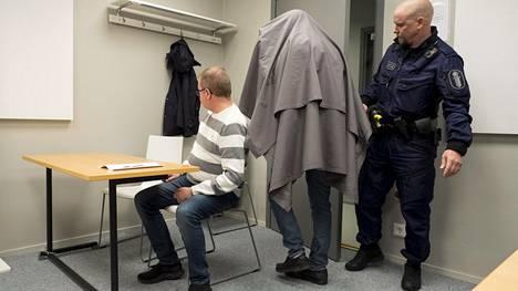 Syytetty saapui poliisitalon istuntosaliin verhotuneena lakanaan.