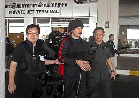 Thaimaalaiset poliisit saattelivat Viktor Boutin (kesk.) Yhdysvaltoihin suunnaneeseen koneeseen.