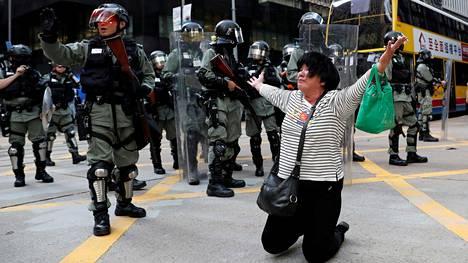 Nainen itkee ja rukoilee mellakkapoliisin edessä tiistaina.