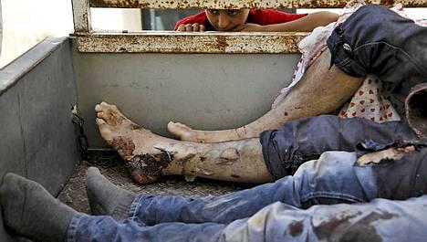 Syyrialainen poika katseli auton lavalle nostettujen uhrien jalkoja.